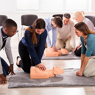 woman and man performing CPR on two dummies while classmates watch